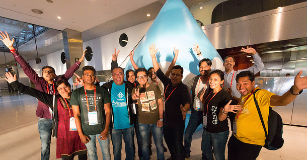 The DrupalCon Asia team cheering with Druplicon