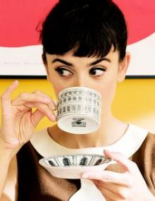 Audrey Hepburn drinking a cup of tea and looking at her extended pinky.